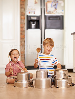 Buy stock photo Two young brothers testing their musical skills on kitchen utensils