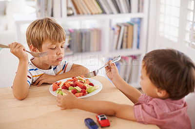 Buy stock photo Two adorable little brothers share a bowl of fruit salad at home