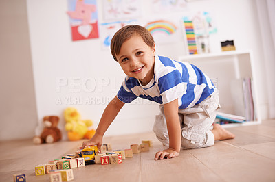 Buy stock photo Portrait of a cute little boy playing with his building blocks and toys in his room