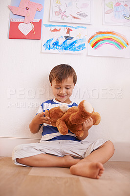 Buy stock photo Shot of a little boy playing with his teddybear in his room