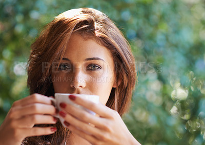 Buy stock photo Portrait of an attractive young woman relaxing outdoors with a cup of coffee