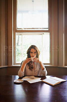 Buy stock photo Portrait of an attractive young author enjoying a cup of coffee while writing indoors