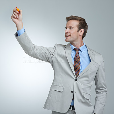 Buy stock photo Studio shot of a young businessman about to write something in the air with a marker