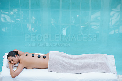 Buy stock photo Shot of aan attractive woman lying on a poolside massage table