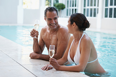 Buy stock photo Cropped shot of a loving mature couple drinking champagne while relaxing in a swimming pool