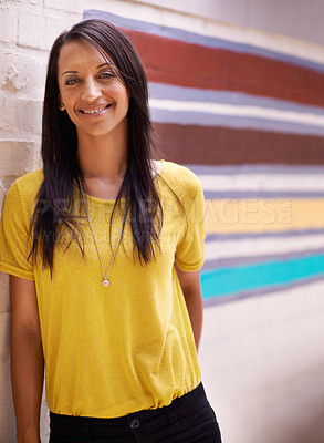 Buy stock photo Shot of an attractive ethnic woman leaning against a colorful wall