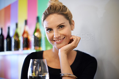 Buy stock photo Portrait of an attractive young woman enjoying a glass of wine at a restaurant
