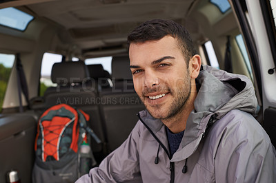 Buy stock photo Portrait of a handsome young hiker sitting at the bank of a car before his hike
