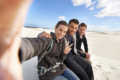 Buy stock photo Shot of a group of friends sitting on their car while on a roadtrip