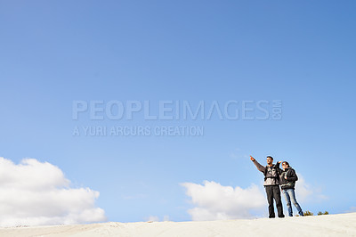Buy stock photo Shot of a happy couple hiking in the dunes together