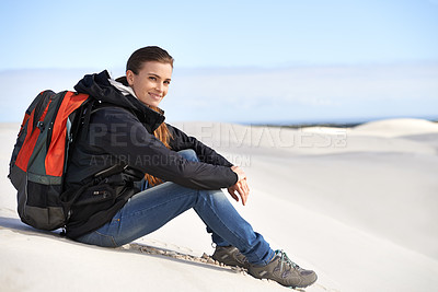 Buy stock photo Shot of an attractive young woman taking a break from her hike on the sand dunes