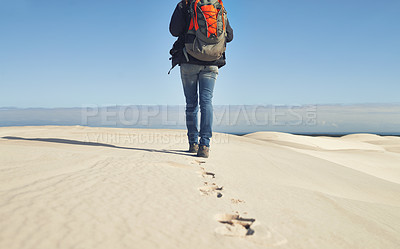 Buy stock photo Rearview shot of a young female hiker walking along the sand dunes