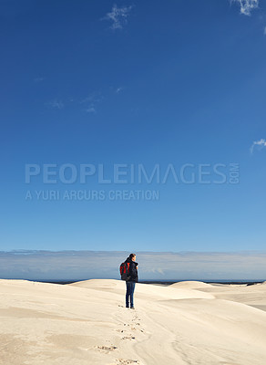 Buy stock photo Shot of a young female hiker walking along the sand dunes