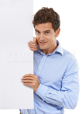 Buy stock photo Portrait of a handsome young man in a studio holding on to the side of a sign board