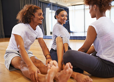 Buy stock photo Shot of three young women dancers stretching on the floor