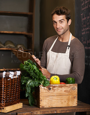 Buy stock photo A young man with a clipboard standing beside a crate full of vegetables