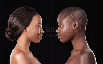 Buy stock photo Two beautiful african women standing face to face against a black background