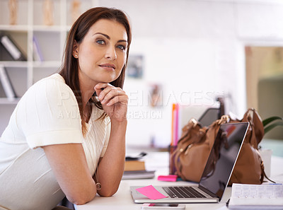 Buy stock photo A young businesswoman smiling at the camera with her hand on her chin