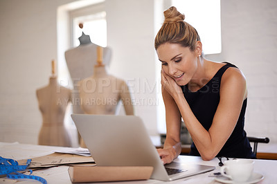 Buy stock photo A young fashion designer speaking on her cellphone while working on a design