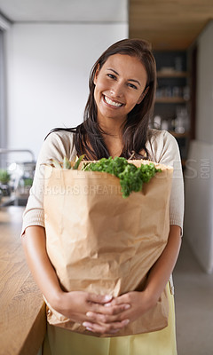 Buy stock photo A young woman standing in her kitchen holding a bag of groceries - portrait