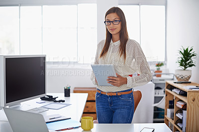 Buy stock photo Portrait of a young woman holding a digital tablet while standing at her desk