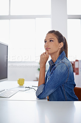 Buy stock photo Shot of a woman sitting thoughtfully at her work station