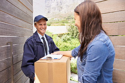 Buy stock photo Shot of a friendly delivery man delivering a package to a young woman