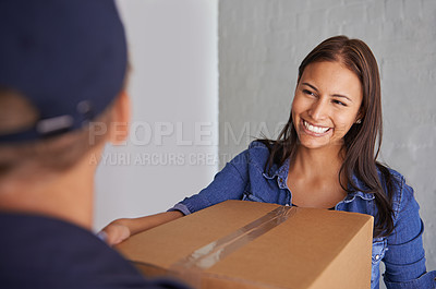 Buy stock photo A beautiful young woman smiling at the camera as she takes a box from a mover