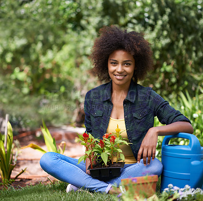 Buy stock photo Portrait of a happy young woman sitting in the garden with a tray of plants and gardening equipment