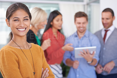 Buy stock photo A portrait of a happy businesswoman standing in an office with her coworkers in the background