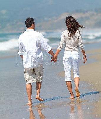 Buy stock photo Beautiful couple walking hand in hand on the beach. On a romantic summer vacation together.