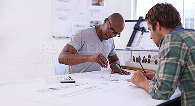 Buy stock photo Shot of two male architects working together on building plans