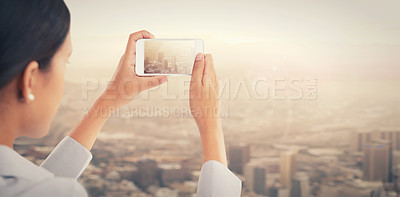 Buy stock photo Rear view of a young woman taking a picture of a cityscape with a smartphone
