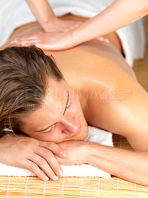 Buy stock photo Happy handsome man getting a back massage by female hands. Enjoying a holiday at the beauty spa.