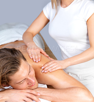 Buy stock photo Portrait of a happy young man with eyes closed receiving shoulder massage from a female therapist