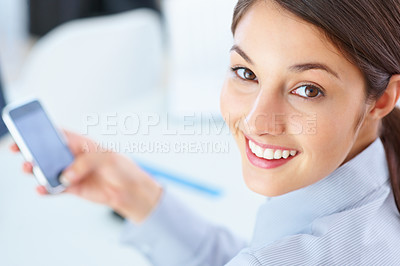 Buy stock photo Closeup of female executive using mobile phone and giving you cute smile