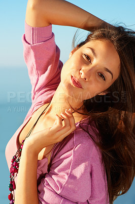 Buy stock photo Portrait of beautiful young girl posing with hand behind head against sky