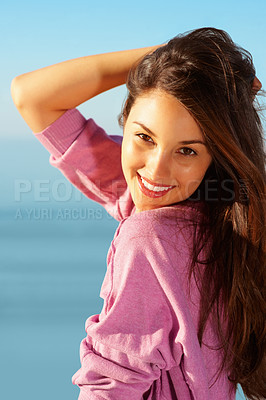 Buy stock photo Portrait of young girl posing outdoors with hand behind head and giving you cute smile