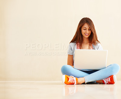 Buy stock photo Full length of beautiful young girl sitting on the floor and using laptop - copyspace