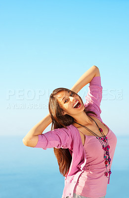 Buy stock photo Portrait of young female with hands behind head standing against sky