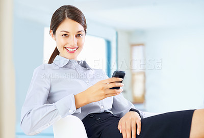 Buy stock photo Portrait of young smiling executive sitting on chair and using cellphone