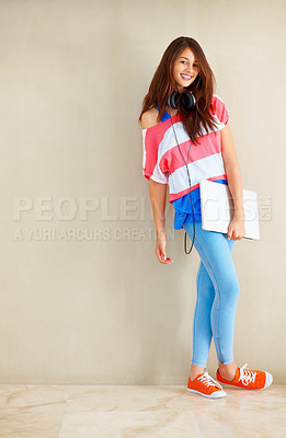 Buy stock photo Full length of attractive young woman standing near wall and holding laptop with one hand
