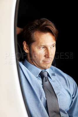 Buy stock photo Portrait of a handsome male executive sitting on chair and looking away