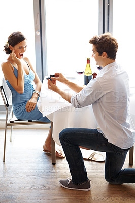 Buy stock photo Happy young male proposing with an engagement ring to his surprised girlfriend in a restaurant