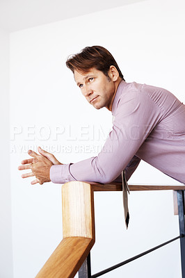 Buy stock photo Portrait of a young businessman leaning on railing and looking away at copyspace