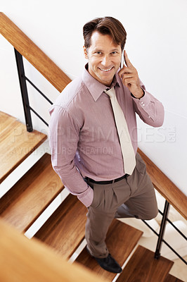 Buy stock photo Portrait of a young businessman walking down the stairs speaking on cellphone