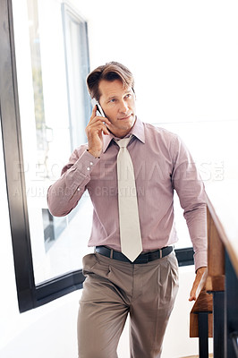 Buy stock photo Portrait of a smart young male business executive talking on cellphone