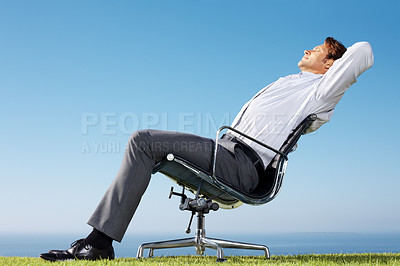 Buy stock photo Portrait of a relaxed young male entrepreneur on chair in green field against sky