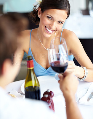 Buy stock photo Portrait of a stylish young woman looking lovingly at her boyfriend while celebrating with wine in a restaurant