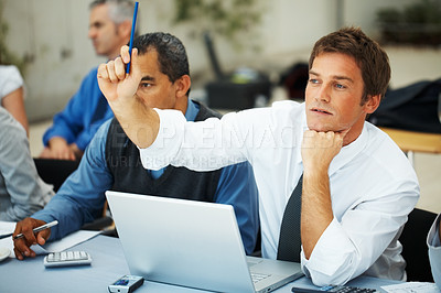Buy stock photo Male executive raising pen while sitting amongst colleagues